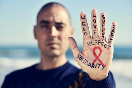 사랑과 지원, 보살핌, 존경과 연대, 에이즈에 대항하기위한 빨간 리본이 달린 젊은 백인 남자의 손의 근접 촬영이 그려져 있습니다. 스톡 콘텐츠