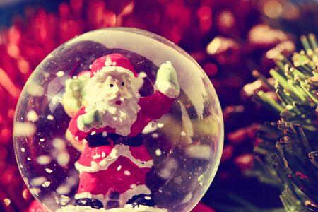 neige noel: gros plan d'un globe de neige de Noël avec un père noël en elle et d'autres ornements de noël Banque d'images