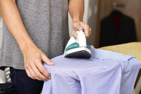 soltería: Primer plano de un hombre joven que plancha una camisa a rayas con una plancha eléctrica Foto de archivo