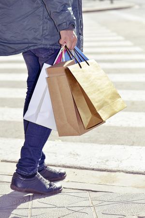compras compulsivas: un hombre caucásico joven que lleva a algunos diferentes bolsas de papel en la calle