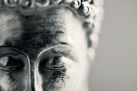 buddhism prayer belief: detail of the face of a representation of the buddha with his eyes closed in duotone