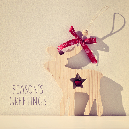 a rustic wooden reindeer-shaped ornament and the text seasons greetings, filtered