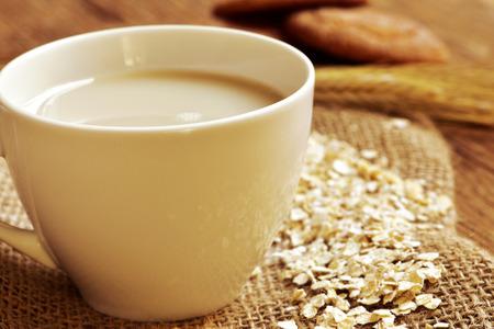 avena en hojuelas: Primer plano de una taza con leche de avena y algunos copos de avena en una mesa de madera rústica y unas galletas digestivas en el fondo