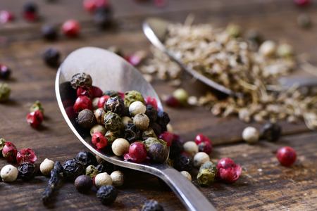 peppertree: closeup of a spoon with a variety of different peppercorns, such as pink pepper, black pepper, red pepper or white pepper, on a rustic wooden table Stock Photo