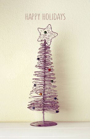 A Simplified Christmas Tree Made Of Wire Against A White Wall ...