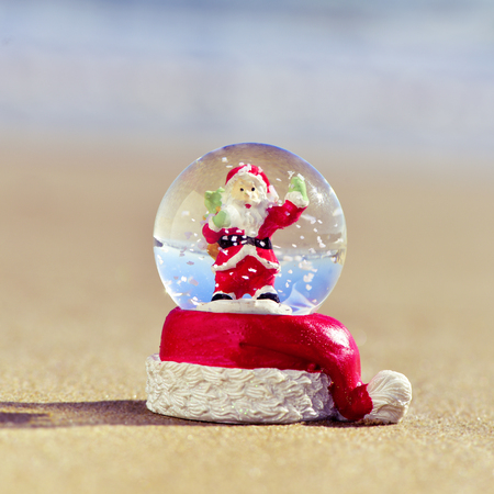 snowdome: closeup of a christmas snow globe with a santa claus in it on the sand of a beach Stock Photo