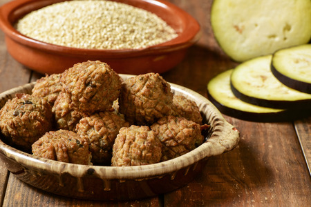 some vegan meatballs in an earthenware plate on a rustic wooden table, with some vegetables in the background Imagens - 49158887