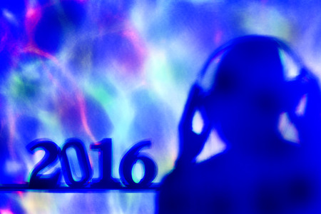 disc jockey: colorful lights projected on the number 2016, as the new year, and a disc jockey man wearing headphones in a dance club