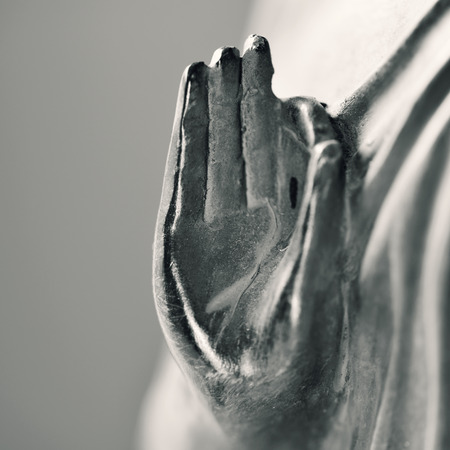 buddhism prayer belief: detail of a representation of the buddha with his hand in gyan mudra in duotone