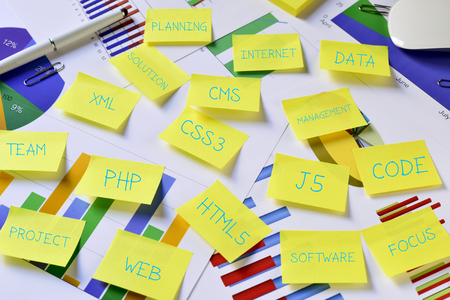 html5: some sticky notes with internet concepts, such as web, project, PHP, CSS3, CMS, HTML5 or J5, on an office desk full of charts Stock Photo