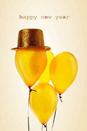 hat new year happy new year festive: text happy new year and a bunch of festive golden balloons, one of them with a golden top hat, on a beige background