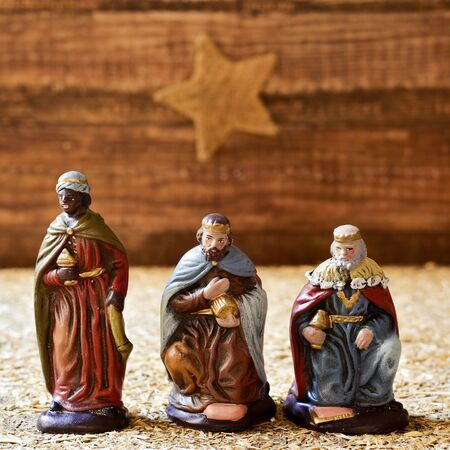 three presents: closeup of the three kings carrying their gifts, and the christmas star in the background, on a rustic scene