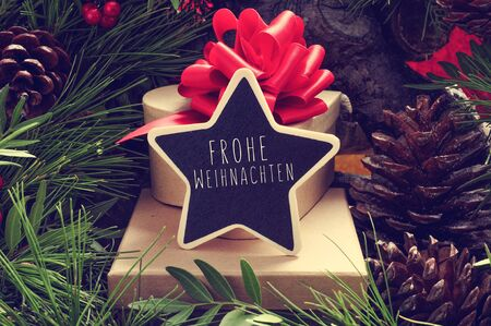 frohe: a star-shaped chalkboard with the text Frohe Weihnachten, Merry Christmas in german, on a pile of gifts placed under the christmas tree and surrounded by natural ornaments such as pine cones Stock Photo