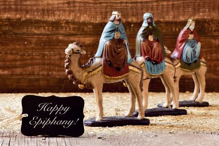 dromedaries: a black label with the text happy epiphany and the three kings on their camels Stock Photo