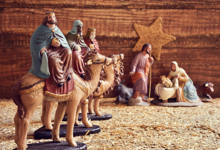 reyes magos: los tres reyes en sus camellos y la sagrada familia en un pesebre rústico Foto de archivo
