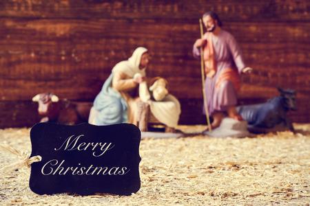 sacra famiglia: una etichetta nera con il testo Buon Natale e la sacra famiglia in un presepe rustico