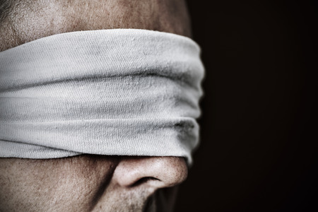 repression: closeup of a young man with a blindfold in his eyes, as a symbol of oppression or repression, with a dramatic effect