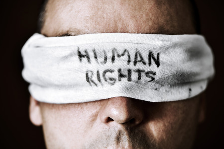 oppression: closeup of a young man with a blindfold in his eyes with the text human rights written in it, as a symbol of oppression or repression, with a dramatic effect