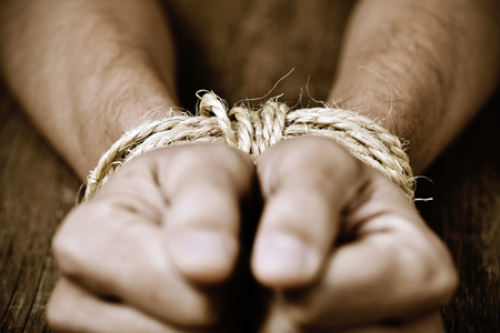 oppression: closeup of the hands of a young man tied with rope, as a symbol of oppression or repression, with a dramatic effect Stock Photo