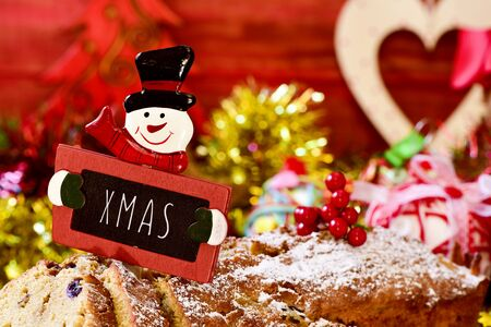 fruitcake: closeup of a fruitcake topped with a snowman-shaped chalkboard with the text xmas, on a table full of christmas gifts and ornaments