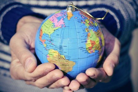 asylum: closeup of a young caucasian man with a world globe with a golden string as a christmas ball in his hands Stock Photo