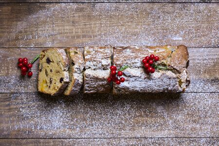 fruitcake: high-angle shot of a fruitcake for christmas time sprinkled with icing sugar, placed on a wooden rustic surface Stock Photo