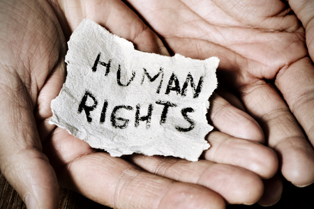 dissent: closeup of the hands of a young man with a piece of paper with the text human rights written in it, with a dramatic effect