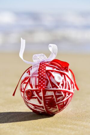 christmas ornamentation: a handmade christmas ball, made with different ribbons and buttons, on the sand of a beach Stock Photo