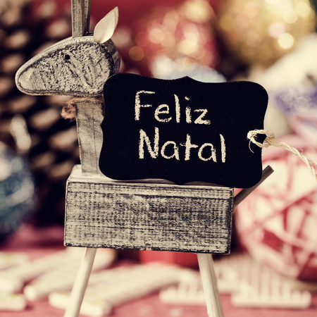 wooden reindeer: a black label with the text feliz natal, merry christmas in portuguese, on a rustic wooden reindeer, with some different christmas ornaments in the background