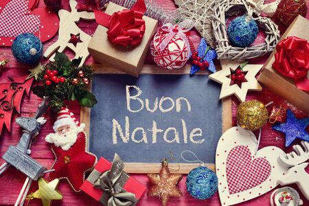 bonnie: high-angle shot of a chalkboard with the text buon natale, merry christmas in italian, surrounded by a pile of gifts and different bonnie christmas ornaments