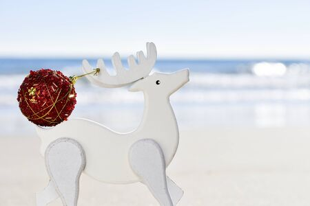 wooden reindeer: closeup of a red christmas ball in the antler of a white wooden reindeer, with the sea in the background Stock Photo