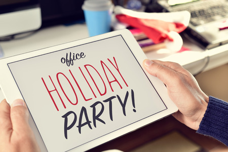 closeup of the hands of a young man at his office holding a tablet with the text office holiday party in its screen Stock Photo