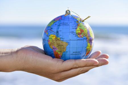 close-up van een jonge blanke man met een wereldbol met een gouden koord als een kerst bal in zijn hand, met de zee op de achtergrond Stockfoto