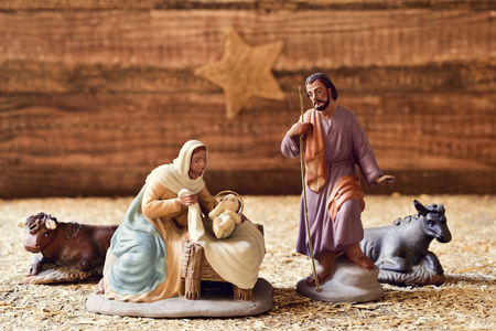 saint: the holy family, Child Jesus, the Virgin Mary and Saint Joseph, and the donkey and the ox in a rustic nativity scene, with the star in the background