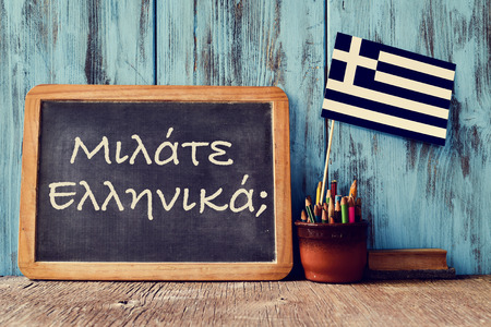greek alphabet: a chalkboard with the question question do you speak greek? written in greek, a pot with pencils, an eraser and the flag of Greece, on a wooden desk