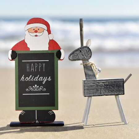 wooden reindeer: a rustic wooden reindeer and a chalkboard in the shape of santa claus with the text happy holidays written in it on the sand of a beach Stock Photo