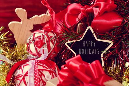 wooden reindeer: star-shaped chalkboard with the text happy holidays surrounded by a pile of gifts, and some different christmas ornaments, such as tinsel, baubles or a wooden reindeer