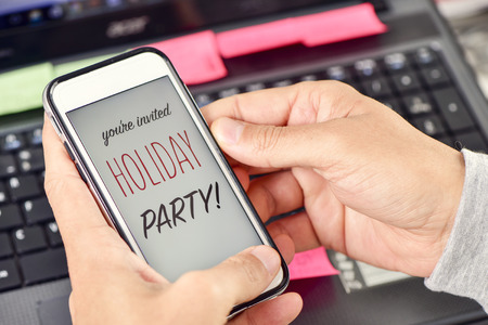you are invited: closeup of the hands of a young man at his office holding a smartphone with the text you are invited holiday party in its screen Stock Photo