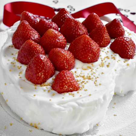 japanese cookery: closeup of a heart-shaped cake covered with cream and topped with strawberries