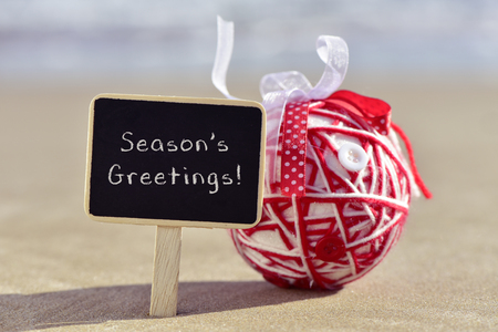 season greetings: a chalkboard with the text seasons greetings and a handmade christmas ball, made with different ribbons and buttons, on the sand of a beach