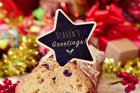 fruitcake: closeup of a fruitcake topped with a star-shaped chalkboard with the text seasons greetings, on a table full of christmas gifts and ornaments