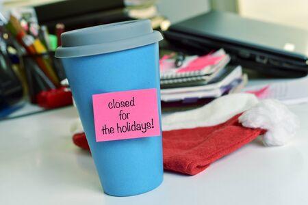 una taza azul con una nota adhesiva de color rosa con el texto texto cerrado para las vacaciones en un escritorio de oficina Foto de archivo