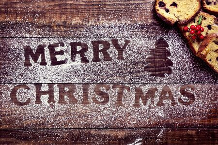 fruitcake: high-angle shot of a wooden table sprinkled with icing sugar where you can read the text merry christmas, and some pieces of fruitcake