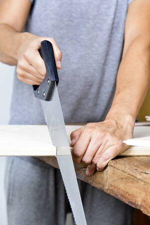 serrucho: primer plano de un hombre cauc�sico joven serrar una tabla de madera con un serrucho