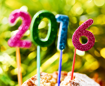 sweet food: closeup of four glittering numbers of different colors forming the number 2016, as the new year, with the focus on the 6, topping a cake