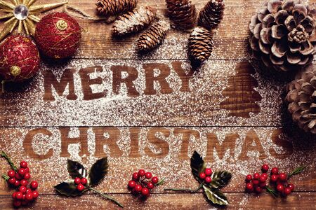 bonnie: high-angle shot of a wooden table sprinkled with icing sugar where you can read the text merry christmas, and some pinecones and other christmas ornaments