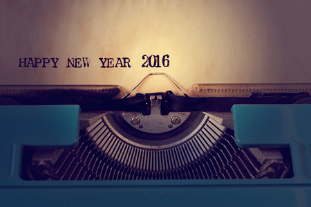 sixteen year old: closeup of a yellowish paper with the text happy new year 2016 in an old blue typewriter