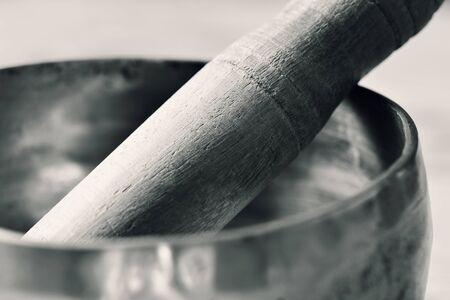 rin gong: closeup of a tibetan singing bowl with its wooden mallet, in duotone