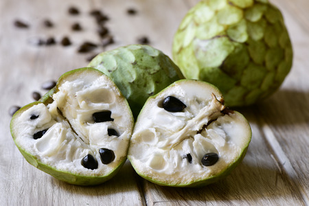 custard apple fruit: closeup of some custard apples, one of them cut in half, on a rustic wooden surface