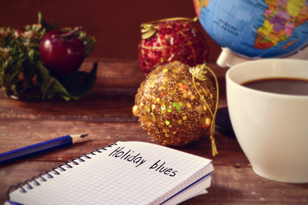 migrated: closeup of a notebook with the text holiday blues written in it on a rustic wooden table with some christmas ornaments, a cup of coffee and a globe